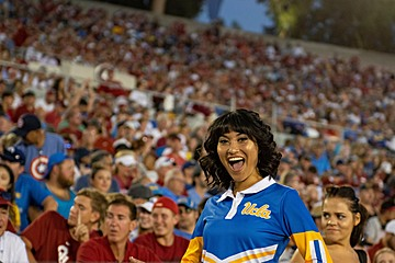 Member of the UCLA Yell Crew wearing her blue uniform, posing in the stands at the Rose Bowl during the UCLA / Oklahoma football game.