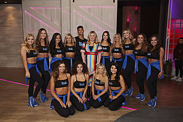 Members of the UCLA Dance Team posed with Kelly Clarkson after performing on her daytime talk show.  Dance Team members are wearing black sports bras and black leggings.