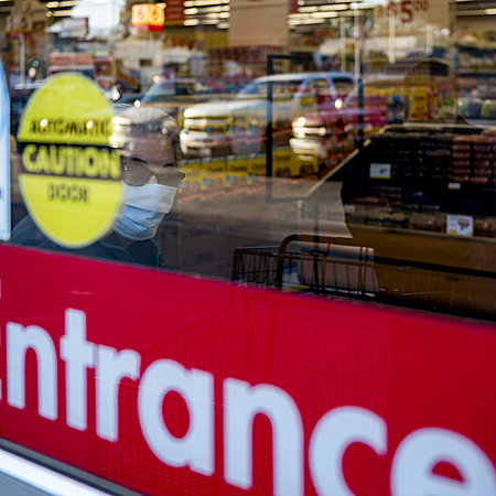 Man with mask on looks through glass door of grocery store