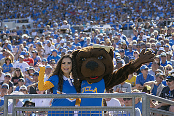 Yell Crew member in a blue uniform posed with Josie Bruin on a perch in the lower level of the Rose Bowl stadium, with thousands of UCLA fans visible behind them