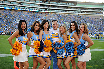 Seven alumni of the Spirit Squad in their original blue and gold uniforms, posing on the field at the Rose Bowl during the Homecoming game.