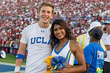 Two members of the UCLA Cheer Squad, standing together in uniform on the field at the Rose Bowl during the UCLA / Oklahoma football game.